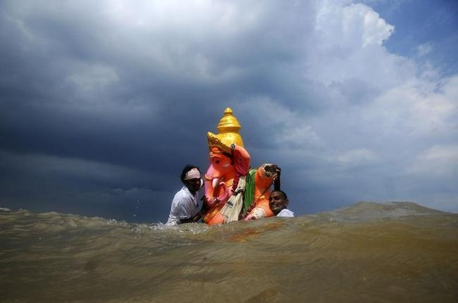 Devotees carry an idol of the Hindu god Ganesh into the Bay of Bengal for its immersion in Chennai