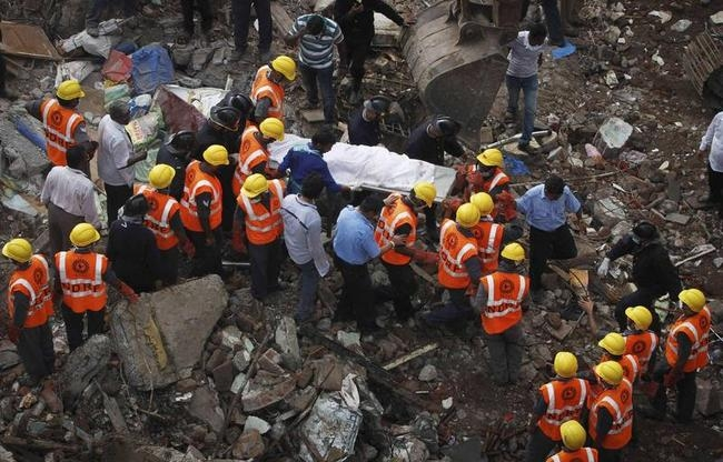 Rescue workers recover a body from site of a collapsed residential building in Mumbai