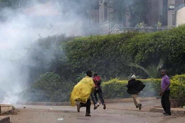 People run from tear gas as security officers disperse a crowd of onlookers near the security perimeter of the Westgate Shopping Centre in Nairobi