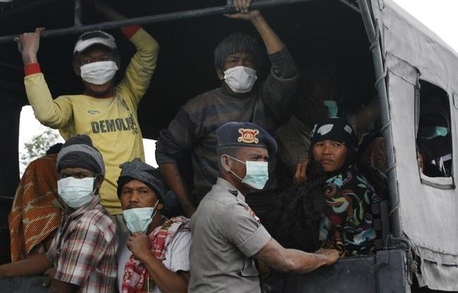Villagers covered in ash sit on a truck while waiting to be evacuated to safety, as Mount Sinabung spews ash and hot lava during an eruption in Perteguhan village