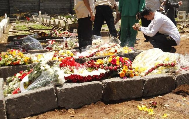 A relative prays at the grave of Kenyan journalist Ruhila Adatia Sood, who was killed in the Westgate shopping mall attack, during her funeral in Nairobi