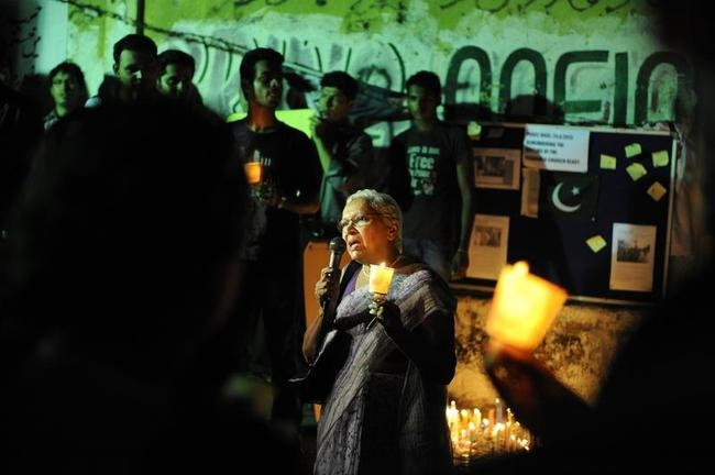 Members of civil society hold candles during a peace vigil to condemn Sunday