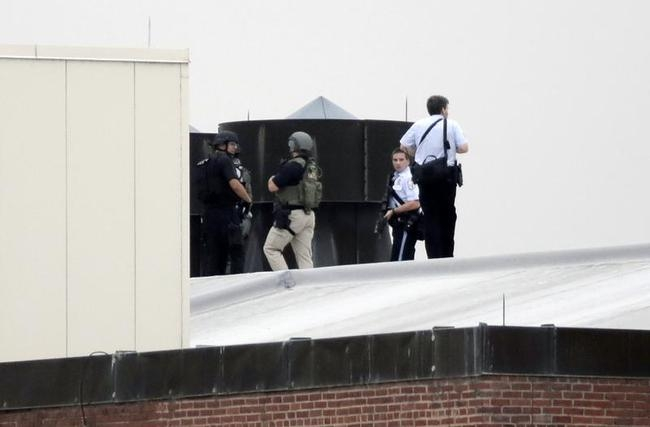Law enforcement officers are deployed on a rooftop as they respond to a shooting on the base at the Navy Yard in Washington