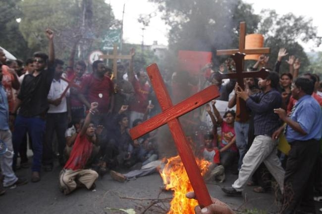 Members of Pakistani Christian community hold crosses in front of a fire during a protest rally to condemn Sunday