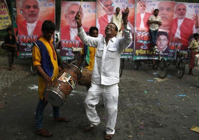 A supporter of BJP celebrates before Narendra Modi was crowned the party