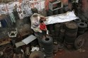 A boy sits on iron plates used in water pumps at a workshop in the old quarters of Delhi