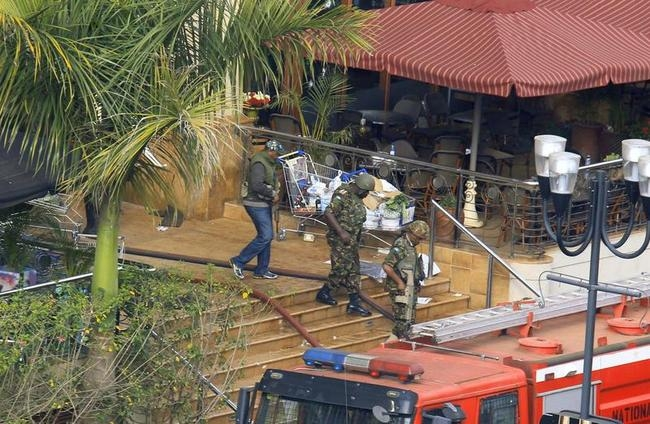 Kenya Defence Forces soldiers leave from the main entrance of Westgate shopping centre after explosions at the mall in Nairobi