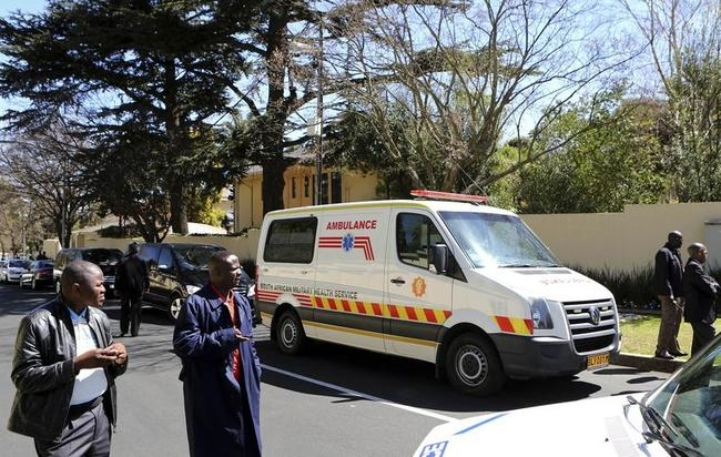 Members of the South African police stand guard near an ambulance that was escorting the ambulance which was believed to be carrying Mandela, outside his house in Houghton, Johannesbur