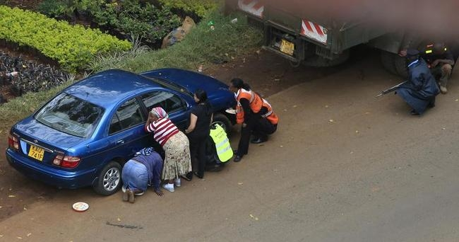 People take cover behind their vehicles along a road during heavy gunfire at Westgate shopping centre in Nairobi