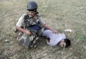 An Indian police officer crouches next to the body of a man killed in a militant attack against a police station in Hiranagar