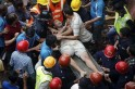 Rescue workers use a stretcher to carry a man who was rescued from the rubble at the site of a collapsed residential building in Mumbai
