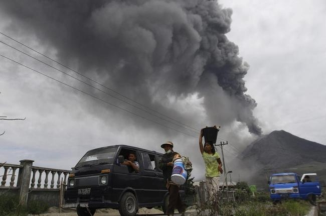 Villagers move to safety as Mount Sinabung spews ash and hot lava during an eruption in Perteguhan village