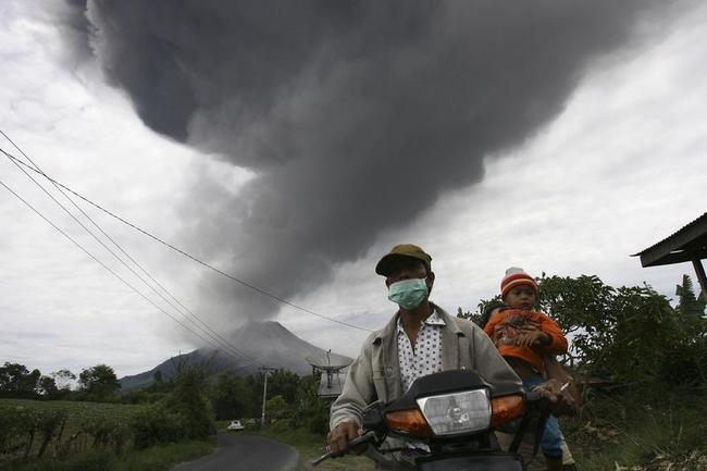 Villagers drive to safety as Mount Sinabung spews ash and hot lava during an eruption in Sukan Debi village in Karo district