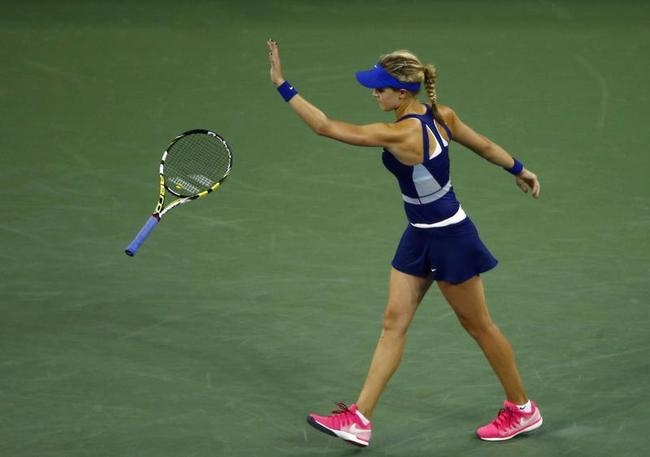 Eugenie Bouchard of Canada tosses her racquet after losing a point to Barbora Zahlavova Strycova of the Czech Republic during their women