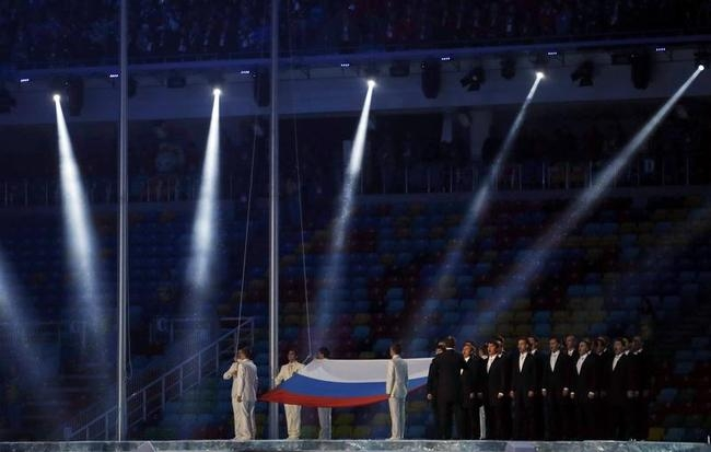 Performers raise the Russian national flag during the opening ceremony of the 2014 Sochi Winter Olympics