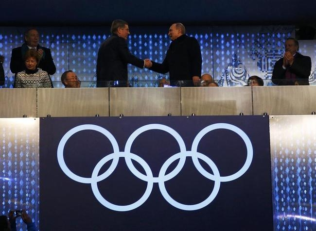 Putin shakes hands with Bach, as Ki-moon looks on during the opening ceremony of the 2014 Sochi Winter Olympics