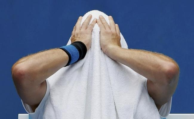 Ernests Gulbis of Lativa holds a towel over his head during a break in play in his men