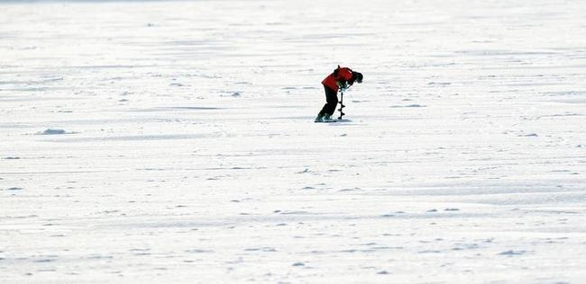 A man uses a power auger to drill a hole in the ice for fishing in Lake Calhoun, Minneapolis