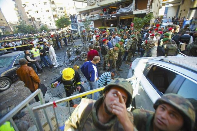 Lebanese army soldiers and civilians gather near the site of an explosion in the Haret Hreik area in the southern suburbs of Beirut