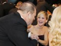 Producer Harvey Weinstein speaks with Jennifer Lawrence during a commercial break at the 20th annual Screen Actors Guild Awards in Los Angeles