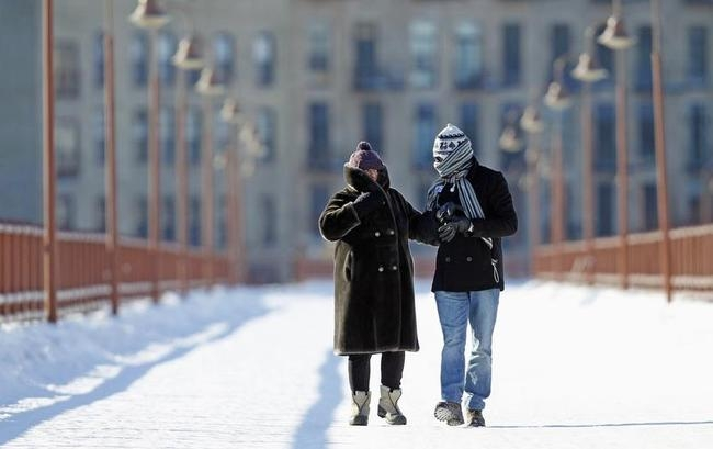 People walk along the windy stone arch bridge which crosses the Mississippi River in Minneapolis