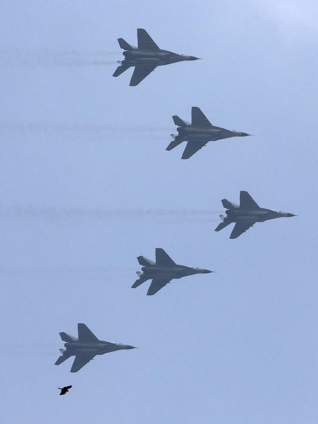 A bird flies below Indian Air Force aircrafts taking part in the full dress rehearsal for the Republic Day parade in New Delhi