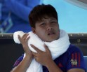 Luksika Kumkhum of Thailand holds an ice-packed towel during a break in play in her women