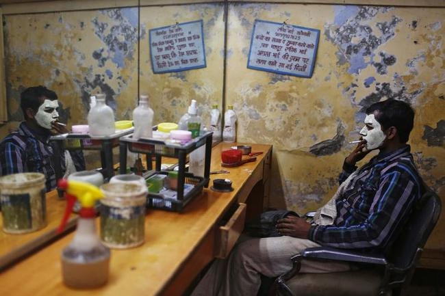 A migrant labourer with his face covered with facial cream, smokes as he waits for the cream to dry at a barber shop in New Delhi