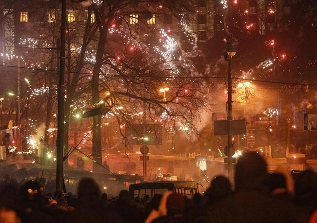 Pro-European protesters watch as fireworks explode near Ukrainian riot police in Kiev