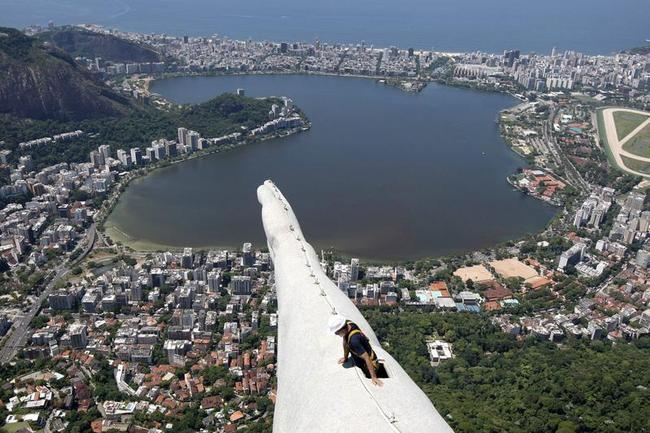 A worker inspects the Christ the Redeemer statue which was damaged during lightning storms in Rio de Janeiro