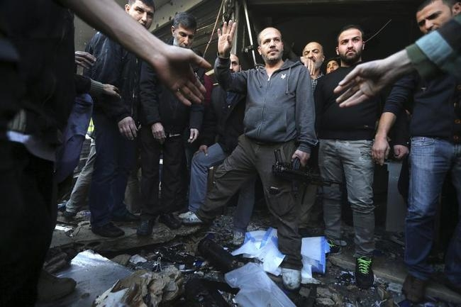 Civilians and Hezbollah members stand at the site of an explosion in the Haret Hreik area, in the southern suburbs of the Lebanese capital Beirut