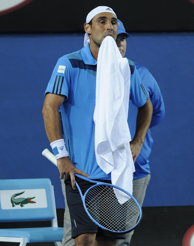 Marcos Baghdatis of Cyprus holds a towel in his mouth