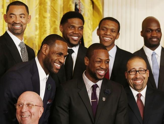 LeBron James and Dwayne Wade join team mates of the 2013 NBA champions Miami Heat as they laugh while U.S. President Barack Obama hosts them in the East Room in Washington