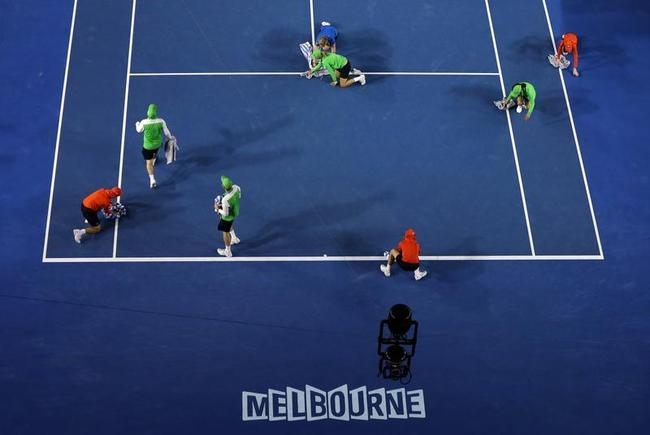 Ground staff dry the court surface of the Rod Laver Arena during rain delay in the quarterfinal between Stanislas Wawrinka
