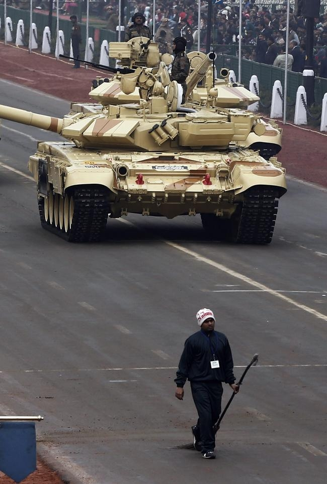A sweeper walks in front of an Indian Army T-90 tank during the full dress rehearsal for the Republic Day parade in New Delhi