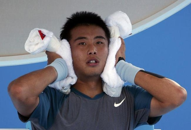 Zhang Ze of China holds an ice-packed towel during a break in play during his men