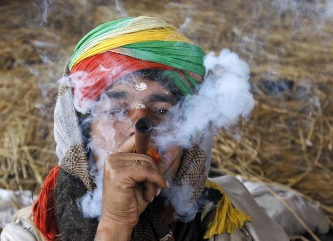A Sadhu or a Hindu holy man, smokes a chillum at Sangam, the confluence of the Ganges, Yamuna and Saraswati rivers, in Allahabad