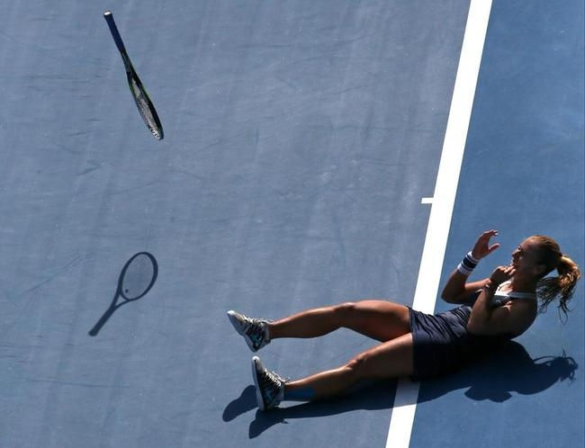 Dominika Cibulkova of Slovakia throws a racket as she celebrates after defeating Agnieszka Radwanska