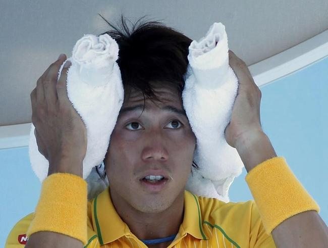 Nishikori of Japan wraps his head in a towel packed with ice during a break in play during his men