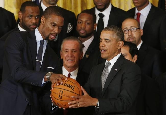Miami Heat player Chris Bosh hands U.S. President Barack Obama an autographed basketball as he honors the NBA basketball champions the Miami Heat at the White House in Washington