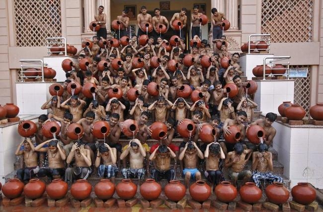 Students pour water on each other as they take a holy bath on the occasion of Magh Purnima in the western Indian city of Ahmedabad