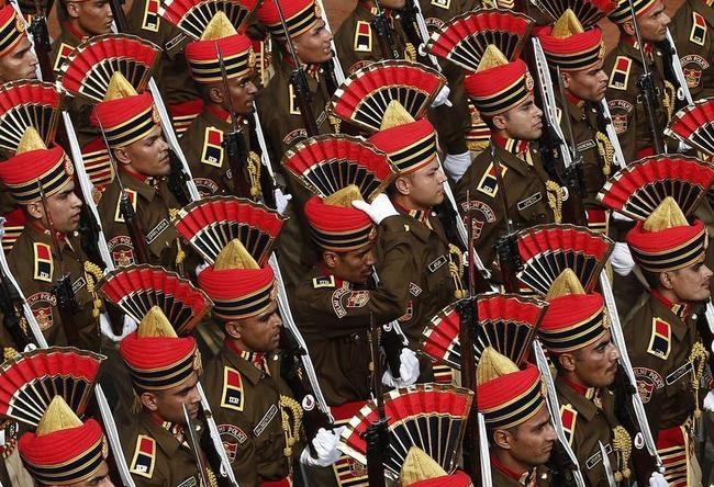 A policeman adjusts his headgear as he marches with others during the full dress rehearsal for the Republic Day parade in New Delhi
