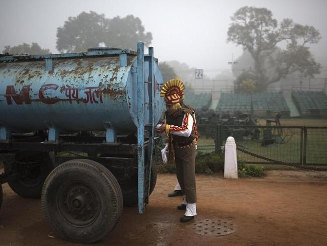 An Indian soldier gets water from tanker after rehearsing for the Republic Day parade amid fog on a cold winter morning in New Delhi