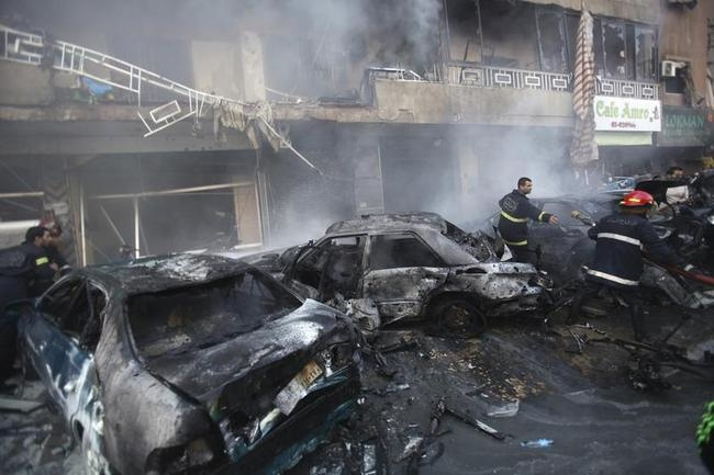 Civil defence members extinguish a fire at the site of an explosion in the Haret Hreik area, in the southern suburbs of the Lebanese capital Beirut