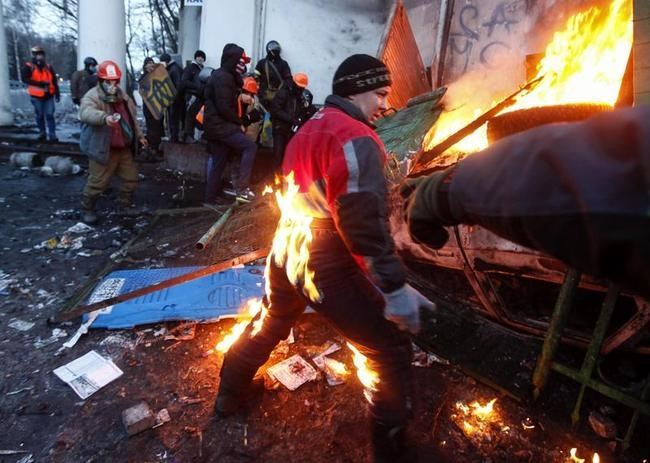 A pro-European integration protester catches fire during clashes with police in Kiev