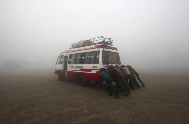Passengers push their bus to start it amid dense fog on a cold winter morning on the outskirts of Agartala