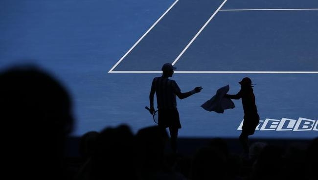 Tomas Berdych of the Czech Republic is silhouetted as he gets a towel form a ball boy during his quarterfinal against David Ferrer