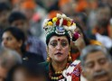 A supporter wearing traditional attire looks on during India