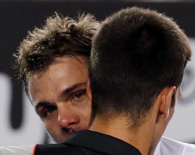 Stanislas Wawrinka of Switzerland hugs Novak Djokovic of Serbia after winning their men