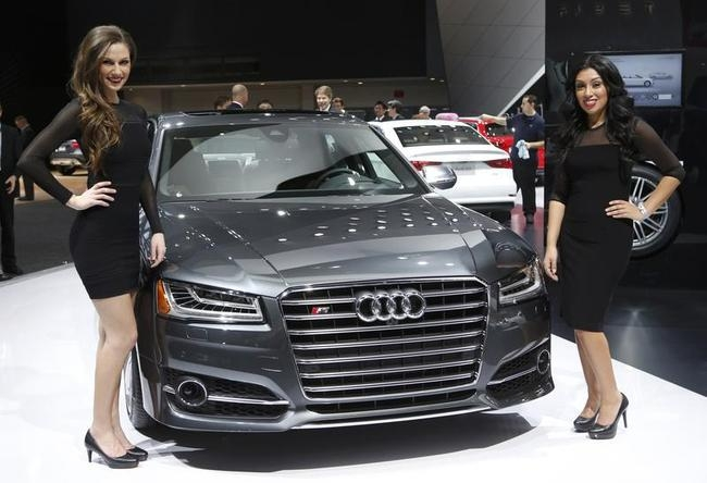 Models pose next to a 2014 Audi S8 during the press preview day of the North American International Auto Show in Detroit